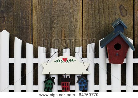 Blank sign hanging on white picket fence with birdhouse