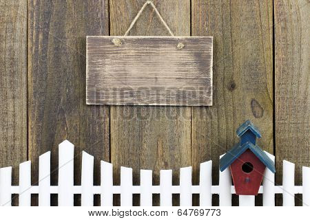 Blank wood sign hanging over white picket fence with birdhouse