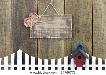 Blank wood sign with red plaid country heart hanging over fence with birdhouse