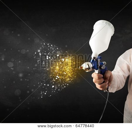 Worker with airbrush painting with glowing golden paint and particles