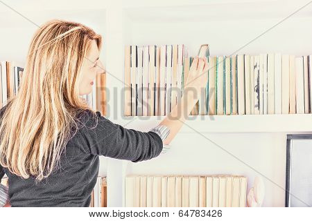 Beautiful Young Woman Taking A Book From Shelf In Library