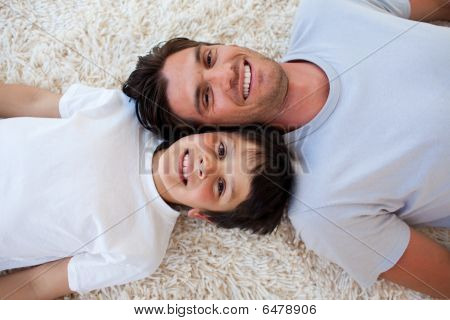 Smiling Father And His Son Lying On The Floor