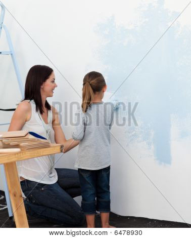 Mother And Her Daughter Painting A Wall Together