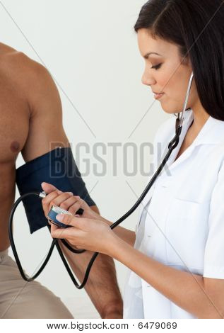 Close-up Of A Female Doctor Checking The Blood Pressure Of A Patient