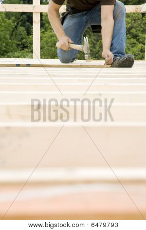 Carpenter Hammering Nail Into Deck