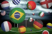 pic of football pitch  - Footballs in various flag colours against football pitch under stormy sky - JPG