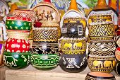stock photo of zulu  - Variety of colorfully painted wooden flowers pots in market - JPG