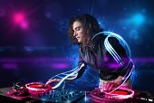 foto of disc jockey  - Beautiful disc jockey playing music with electro light effects and lights - JPG