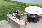 stock photo of red meat  - Father and daughter preparing a barbecue at an outdoor summer kitchen on a paved patio with a garden umbrella table and chairs as they grill the meat on the gas BBQ waiting for guests to arrive - JPG