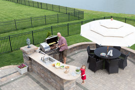 pic of braai  - Father and daughter preparing a barbecue at an outdoor summer kitchen on a paved patio with a garden umbrella table and chairs as they grill the meat on the gas BBQ waiting for guests to arrive - JPG