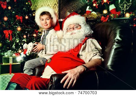 Santa Claus in his everyday clothes in Christmas home decor. Happy little boy helps Santa Claus get ready for Christmas.