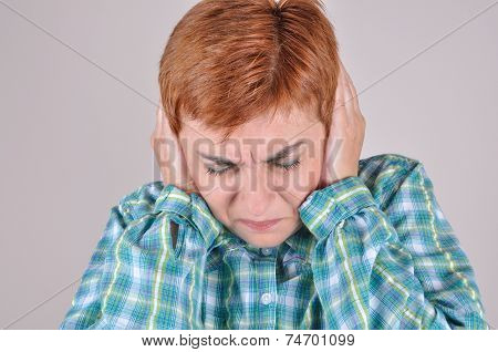 Frowning woman covering her ears with hands