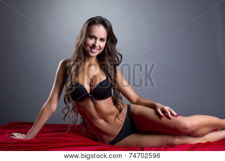 Smiling athletic model posing in lingerie