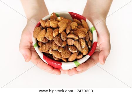 child holding a bowl of almonds