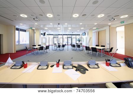 Bright conference room with four tables and modern equipment