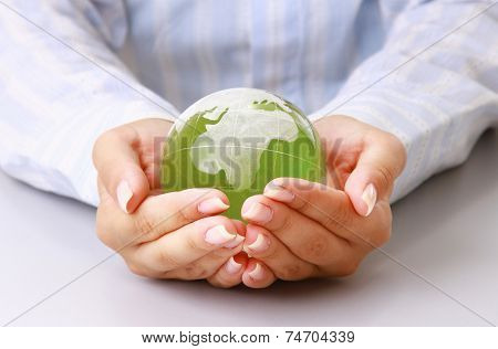 Female hands holding glass earth , isolated on white background.