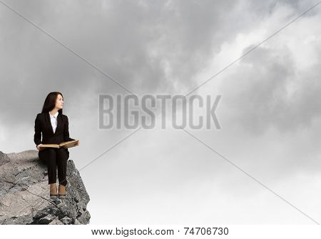 Young businesswoman sitting on rock edge with book in hands