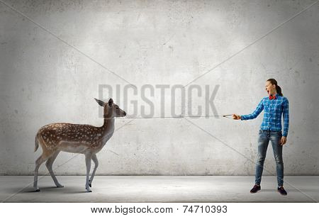 Young woman in casual holding deer on lead