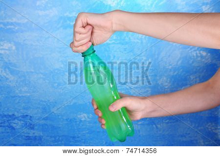 Hand opening bottle with sweet water on blue background