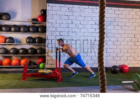 sled push man pushing weights workout exercise