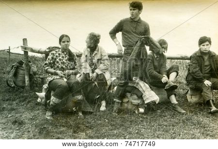 POLAND, CIRCA SIXTIES: Group of young hitchhikers with backpacks waits outdoor for a lift, vintage photo