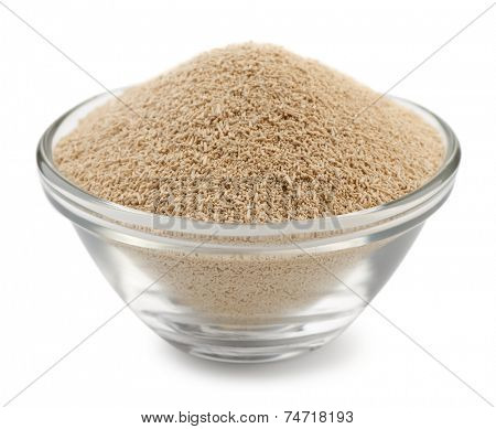 Dry yeast granules in glass bowl isolated on white