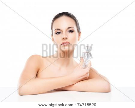 Portrait of beautiful, fresh, healthy and sensual woman with a bottle of perfume essence isolated on white
