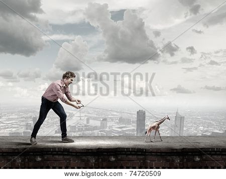 Young man in casual holding giraffe cub on lead