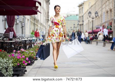 Beautiful young woman in flowers dress, against of summer street