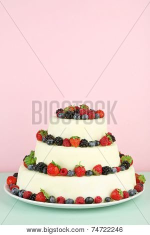 Beautiful wedding cake with berries on pink background