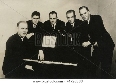 CANADA - CIRCA 1940s: Vintage photo shows musicians near the piano.