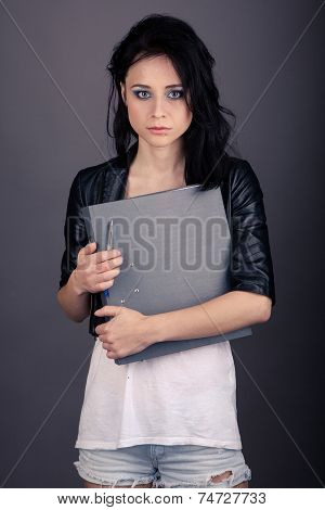 Pretty Girl In Leather Jacket With A Folder For Papers On A Gray Background