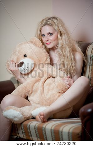 Young blond sensual woman sitting on sofa relaxing with a huge teddy bear. Beautiful girl