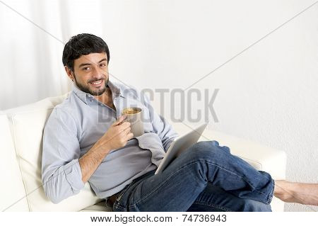 Young Attractive Hispanic Man At Home On White Couch Using Digital Tablet Or Pad