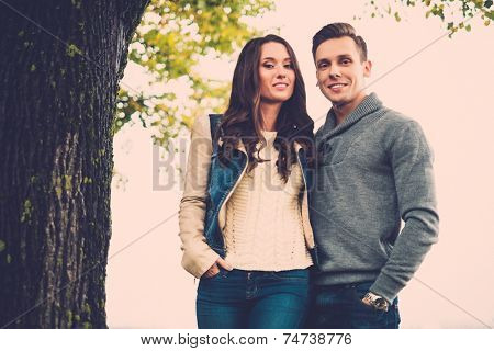 Beautiful young couple on autumn fogy day