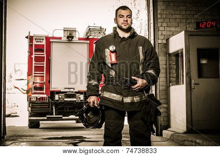 Firefighter against truck in firefighting depot