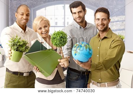 Portrait of happy young businesspeople holding green plants and globe.