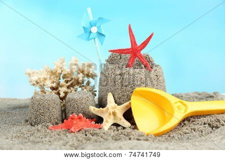 Sandcastle with pinwheel on sandy beach