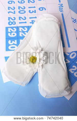 Sanitary pads, calendar and white flower on light blue background