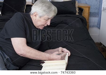 Senior Writing From His Bed