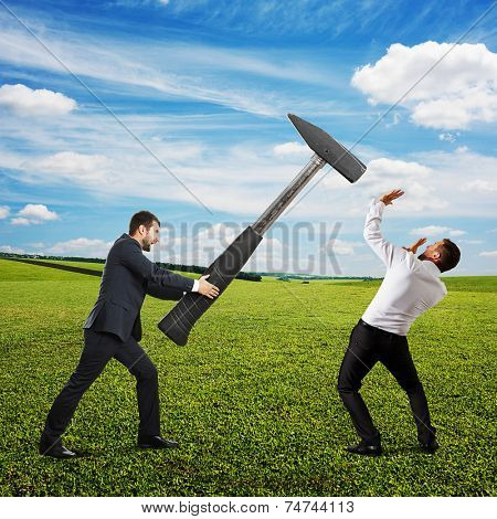 screaming angry businessman hammering startled man at outdoor