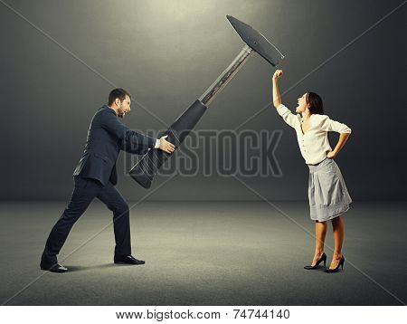 concept photo of conflict between man and woman. angry screaming man holding big hammer and hitting, woman showing fist and shouting. photo over dark background