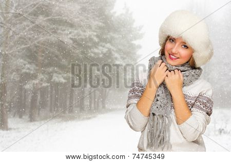 Young woman in fur hat at snowy forest
