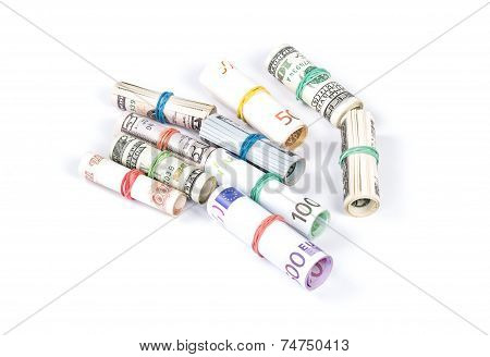 Rolled up Euro and dollar bills on financial paper