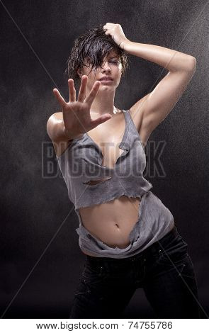 Wet sexy young woman with a torn shirt. Fine spray of water.