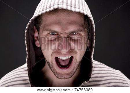 Portrait of young angry screaming man with a hood