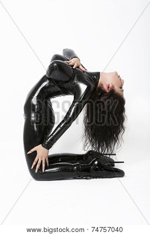 Sexy flexible brunette in black latex and boots whit high heels arching back