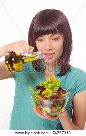Young happy woman making salad with vegetables and oil