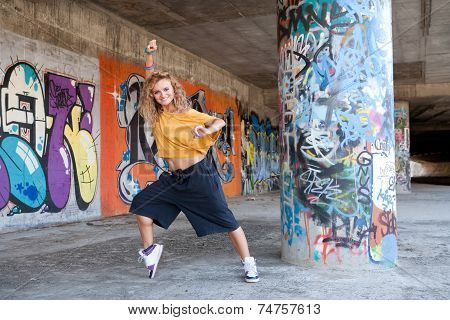Happy hip teenage blonde girl breakdancing by graffiti wall