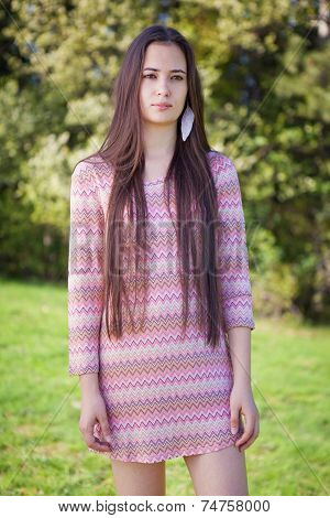 Pretty woman with pink tunic in the park n grass